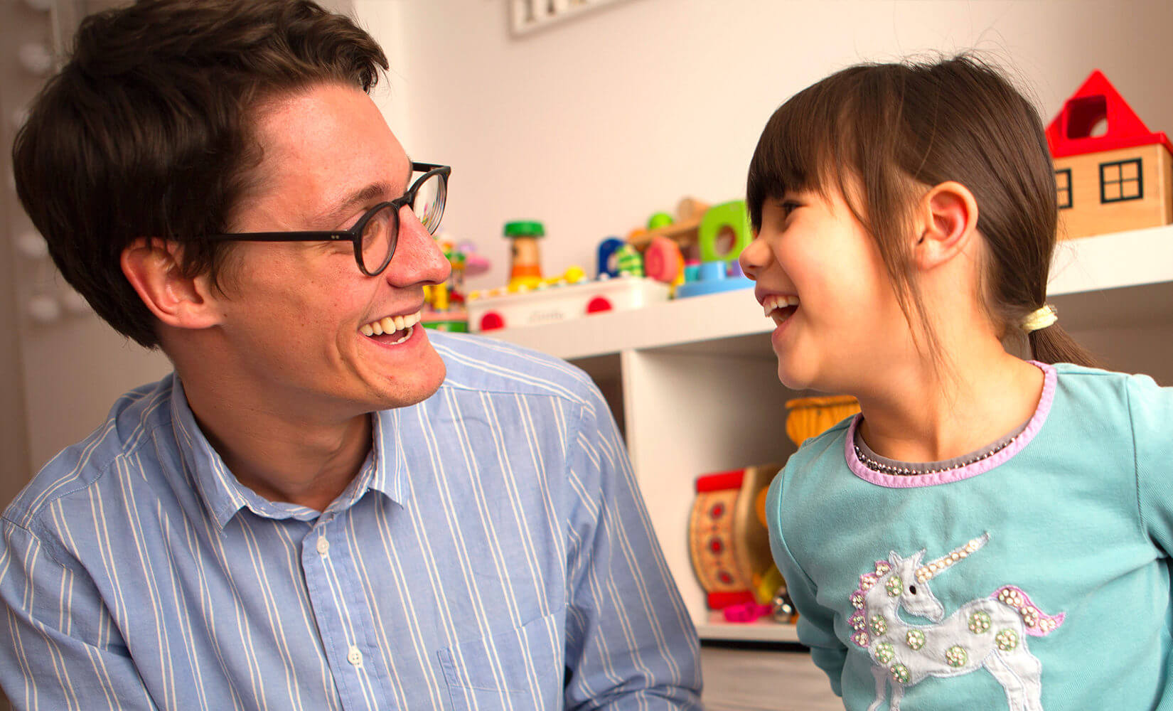home-schooling tutor smiling at young girl